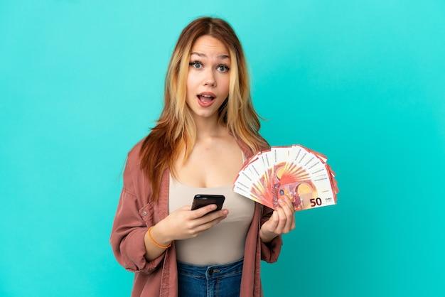 Blondes mädchen des teenagers, das viel euro über isoliertem blauem hintergrund nimmt, überrascht und sendet eine nachricht