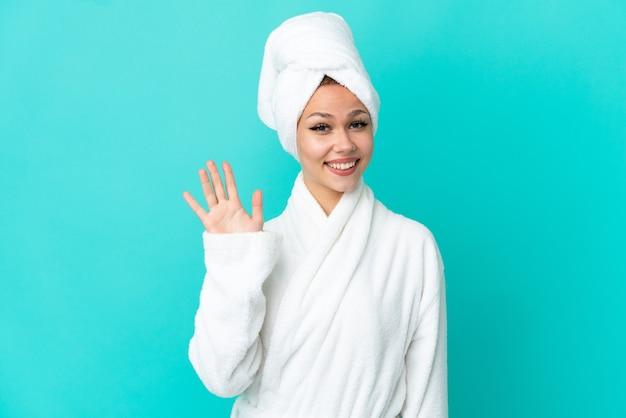 Blondes mädchen des teenagers in einem bademantel über lokalisiertem blauem hintergrund, der mit der hand mit glücklichem ausdruck grüßt