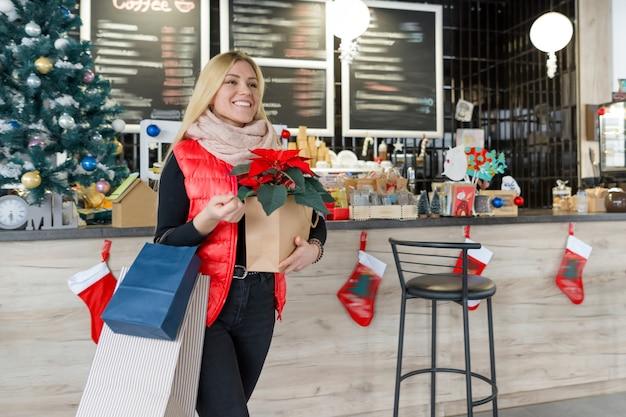 Blondes mädchen des winterporträts mit weihnachtseinkäufen