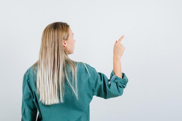 Blondes mädchen dreht sich um und zeigt in grüner bluse nach rechts und sieht charmant aus