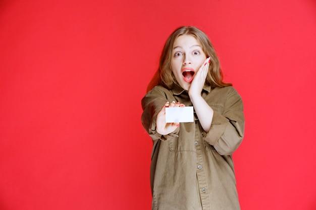 Blondes mädchen erhielt eine visitenkarte und überrascht.