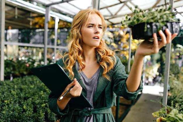 Blondes mädchen, gekleidet in graues t-shirt und dunkelgrünes gewand, hält topf mit pflanze mit kleinen blättern.