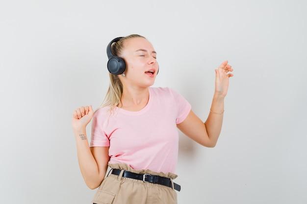 Blondes mädchen genießt musik mit kopfhörern im t-shirt, in der hose und sieht munter aus. vorderansicht.