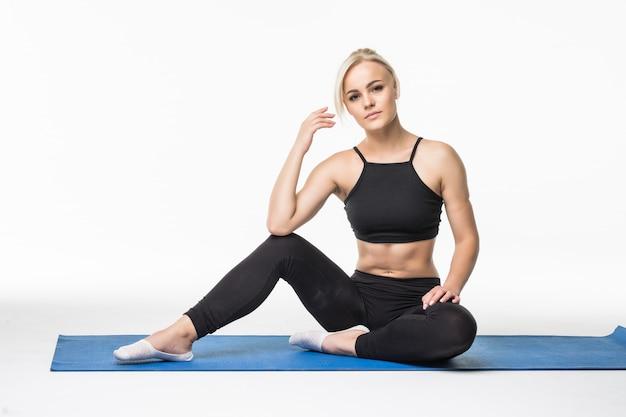 Blondes mädchen haben eine entspannungszeit nach sportübungen auf dem boden, die auf einer sportkarte sitzen
