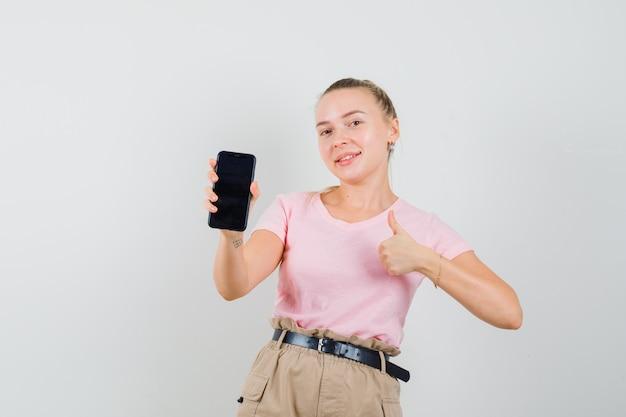 Blondes mädchen hält handy, zeigt daumen oben in t-shirt, hose und schaut lustig. vorderansicht.