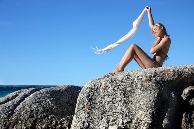 Blondes mädchen im bikini auf seefelsen mit fliegendem foulard