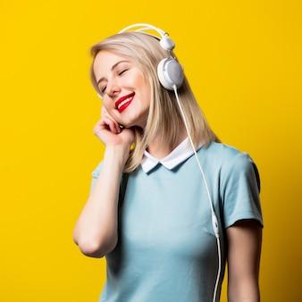 Blondes mädchen im blauen kleid mit kopfhörern auf gelbem raum