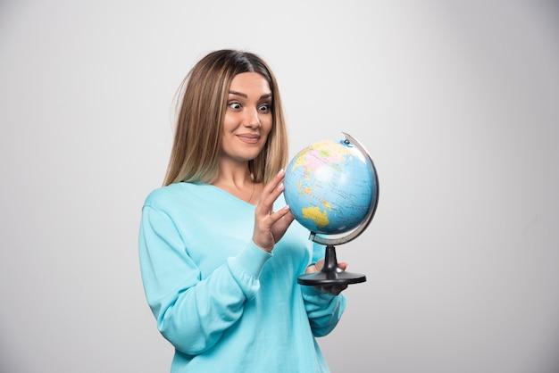 Blondes mädchen im blauen sweatshirt, das einen globus hält, standort errät und spaß hat.