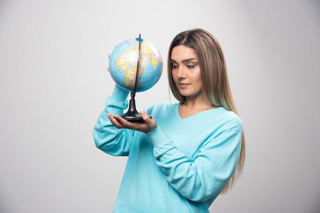 Blondes mädchen im blauen sweatshirt, das einen globus hält und die erdkarte aufmerksam prüft.