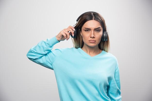 Blondes mädchen im blauen sweatshirt, das kopfhörer trägt und versucht, die musik zu verstehen.