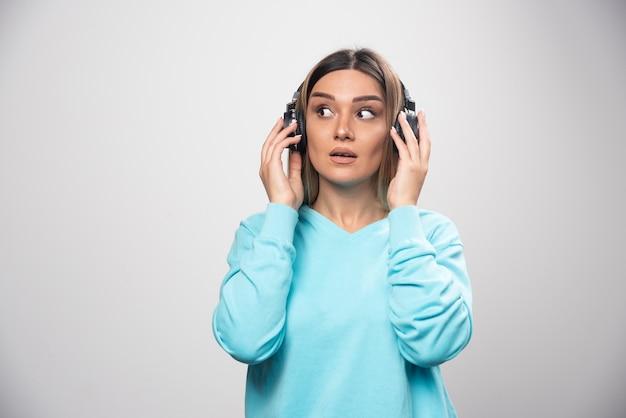Blondes mädchen im blauen sweatshirt, das kopfhörer trägt und versucht, die musik zu verstehen