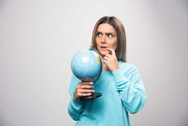 Blondes mädchen im blauen sweatshirt hält einen globus, denkt sorgfältig und versucht sich zu erinnern.
