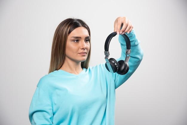 Blondes mädchen im blauen sweatshirt hält kopfhörer und macht sich bereit, sie zu tragen, um die musik zu hören