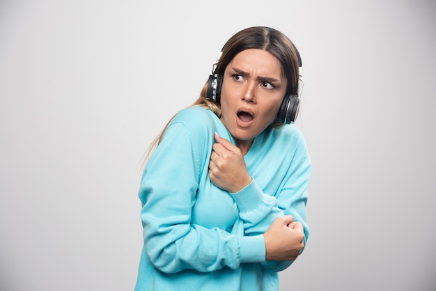 Blondes mädchen im blauen sweatshirt hört die kopfhörer und genießt die musik nicht.