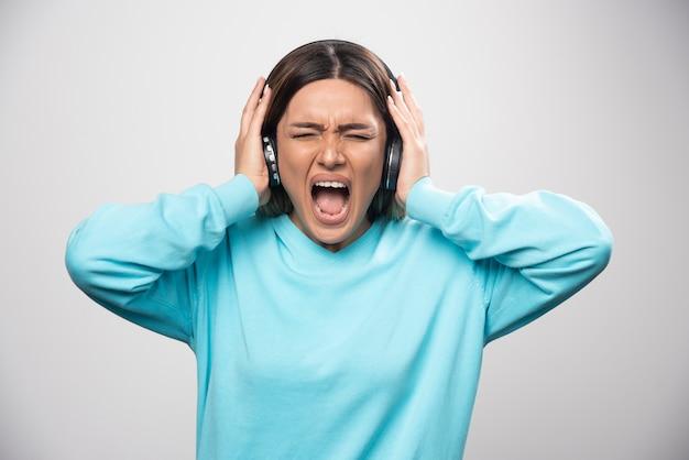 Blondes mädchen im blauen sweatshirt hört die kopfhörer und genießt die musik nicht