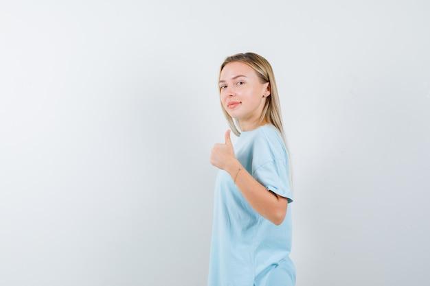 Blondes mädchen im blauen t-shirt, das daumen oben zeigt, über schulter schaut und zuversichtlich schaut, vorderansicht.