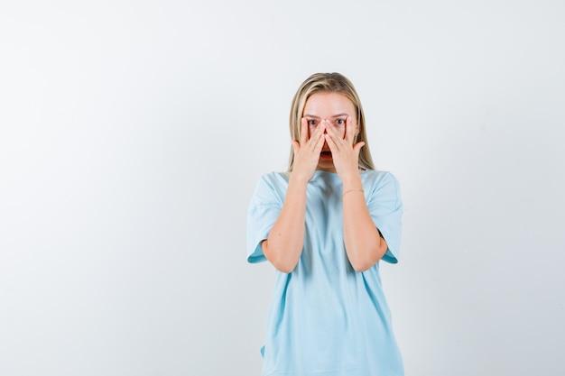 Blondes mädchen im blauen t-shirt, das v zeichen auf den augen zeigt, durch finger schaut und überrascht schaut, vorderansicht.