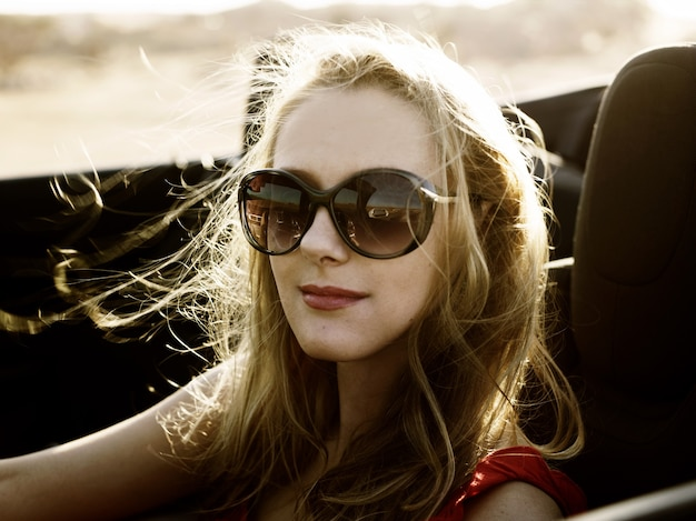 Blondes mädchen im cabrio mit fliegenden haaren und sonnenbrille