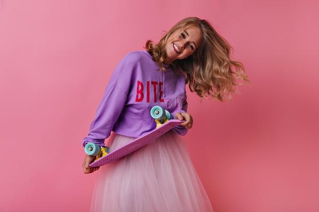 Blondes mädchen im freizeithemd, das skateboard hält und lacht. charmantes weibliches modell, das aufrichtige gefühle auf rosa ausdrückt.