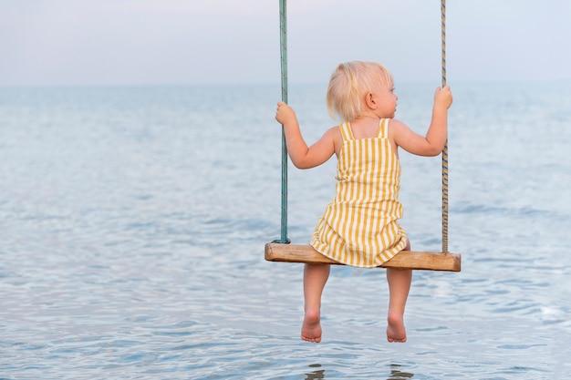 Blondes mädchen im gelben kleid, das auf einer seilschaukel über wasser sitzt. schaukel auf dem meer.