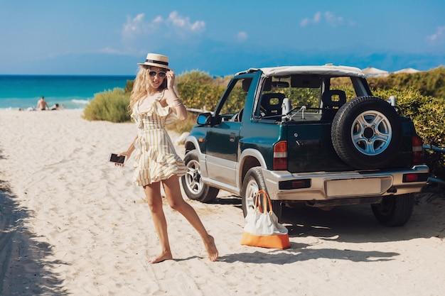 Blondes mädchen im gestreiften kleid, das auf kamera am sandstrand aufwirft