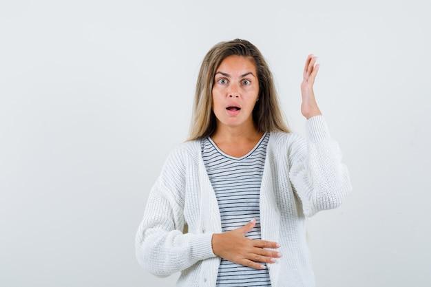 Blondes mädchen im gestreiften t-shirt, in der weißen strickjacke und in der jeanshose, die eine hand auf bauch halten, während sie eine andere hand heben und überrascht, vorderansicht schauen.