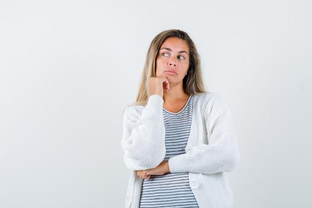Blondes mädchen im gestreiften t-shirt, in der weißen strickjacke und in der jeanshose, die kinn auf hand stützen, während hand unter ellbogen halten und nachdenklich, vorderansicht schauen.