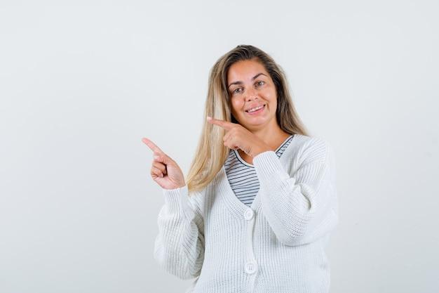 Blondes mädchen im gestreiften t-shirt, in der weißen strickjacke und in der jeanshose, die mit zeigefingern nach links zeigen und glücklich schauen, vorderansicht.