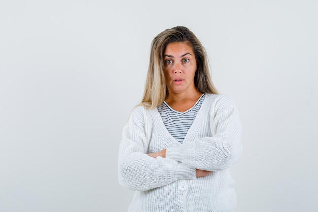 Blondes mädchen im gestreiften t-shirt, in der weißen strickjacke und in der jeanshose stehen arme verschränkt und suchen verführerisch, vorderansicht.