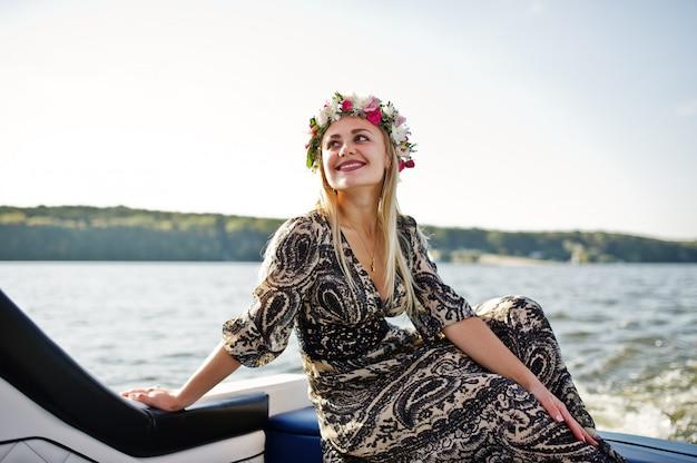 Blondes mädchen im kranz, der auf yacht an der junggesellenabschied sitzt.