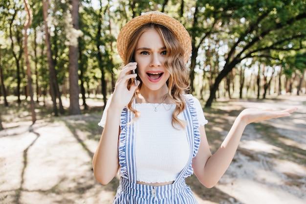 Blondes mädchen im lässigen t-shirt, das emotional am telefon spricht. außenporträt der lustigen lockigen frau, die mit smartphone auf bäumen aufwirft.