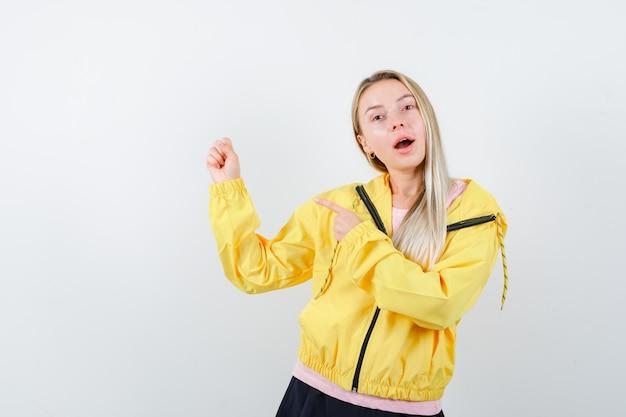 Blondes mädchen im rosa t-shirt und in der gelben jacke ballte die faust und zeigte darauf und sah glücklich aus