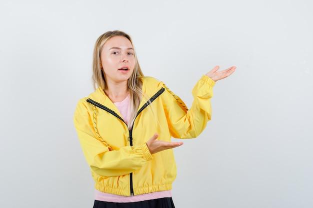 Blondes mädchen im rosa t-shirt und in der gelben jacke, die hände strecken, als etwas präsentieren und ernst schauen