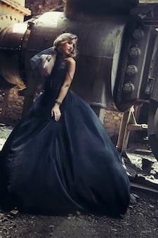 Blondes mädchen im schwarzen kleid an einer alten verlassenen fabrik. steampunk