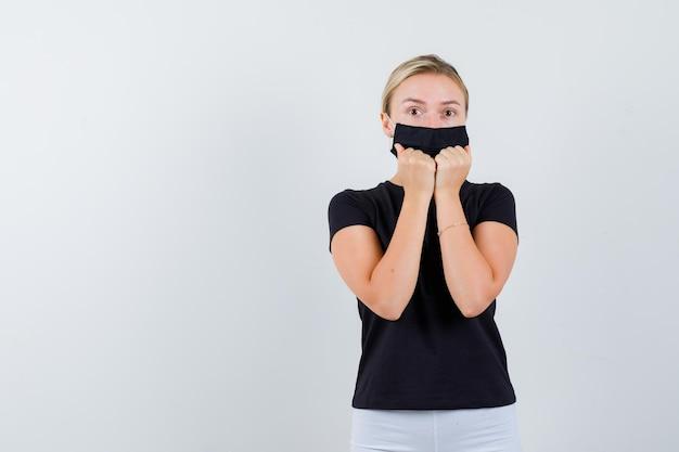 Blondes mädchen im schwarzen t-shirt, weiße hose, schwarze maske, die fäuste isoliert hält