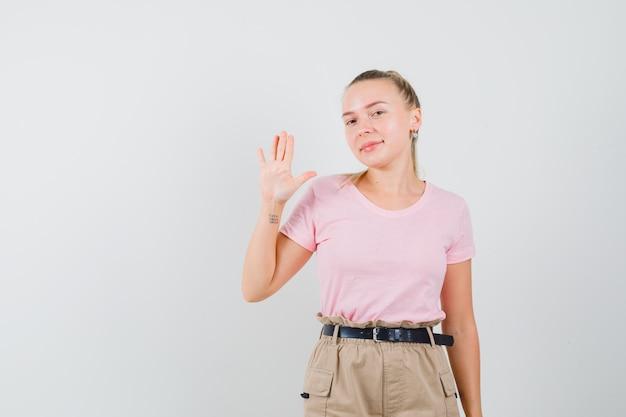 Blondes mädchen im t-shirt, hose winkt hand zum abschied und schaut lustig, vorderansicht.