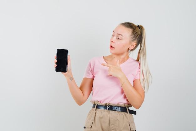 Blondes mädchen im t-shirt, hose zeigt auf handy und schaut konzentriert, vorderansicht.