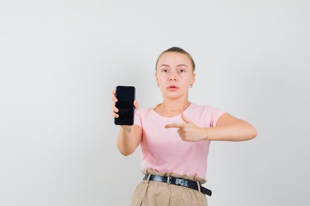 Blondes mädchen im t-shirt, hose zeigt auf handy und schaut verwirrt, vorderansicht.
