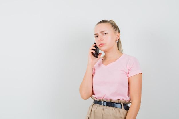 Blondes mädchen im t-shirt, hosen, die auf handy sprechen und traurig schauen, vorderansicht.