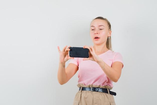 Blondes mädchen im t-shirt, hosen, die foto auf handy, vorderansicht machen.
