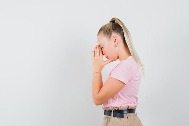 Blondes mädchen im t-shirt, hosen, die hände in der gebetsgeste halten und ruhig schauen.