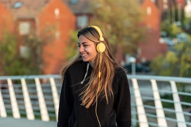 Blondes mädchen im teenageralter mit gelben kopfhörern, die beim gehen auf einer weißen städtischen brücke musik hören. wohngebäude im hintergrund.