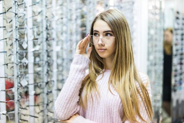 Blondes mädchen im weißen pullover wählen neue medizinische brille im professionellen geschäft