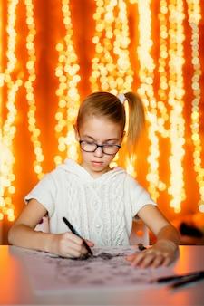 Blondes mädchen im weißen strickkleid und in den großen schwarzen gläsern, die weihnachtsmann zeichnen. thema des neuen jahres