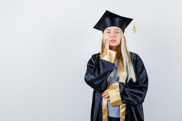 Blondes mädchen in abschlusskleid und mütze, das eine hand in die nähe des mundes legt und eine andere hand auf den bauch hält