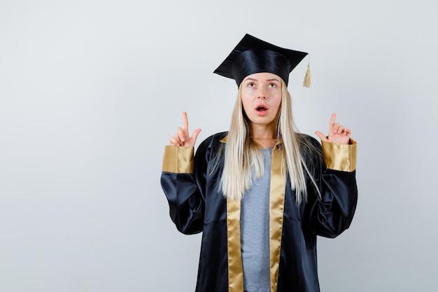 Blondes mädchen in abschlusskleid und mütze, das mit den zeigefingern nach oben zeigt und süß aussieht