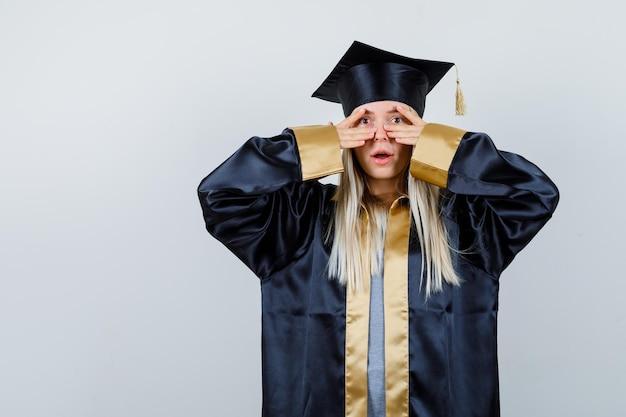 Blondes mädchen in abschlusskleid und mütze, das v-zeichen auf den augen zeigt und überrascht aussieht