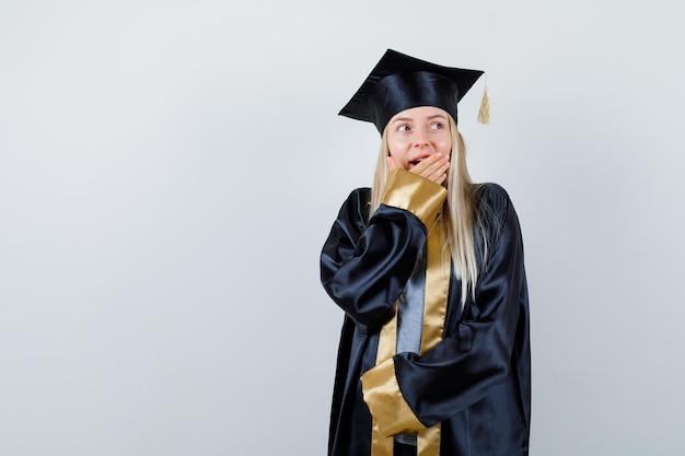 Blondes mädchen in abschlusskleid und mütze, die den mund mit der hand bedeckt, wegschaut und überrascht aussieht
