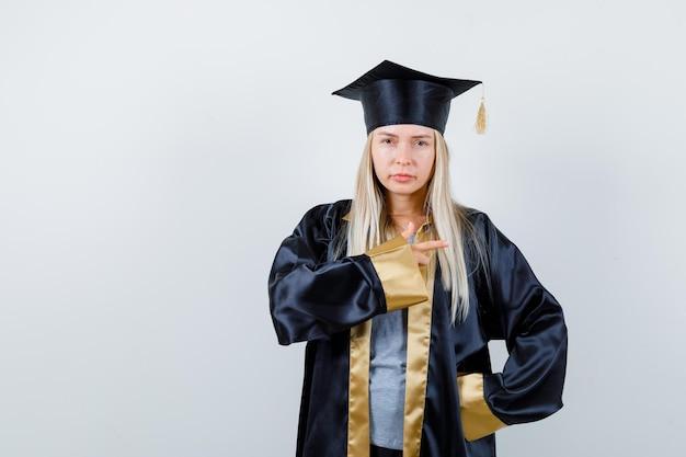 Blondes mädchen in abschlusskleid und mütze, die mit dem zeigefinger nach rechts zeigt und süß aussieht