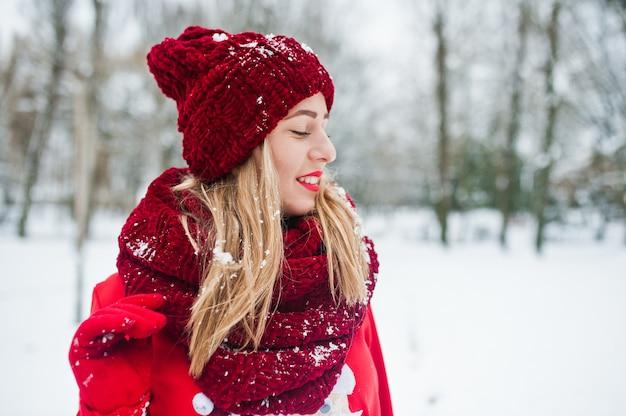 Blondes mädchen in der roten schal-, hut- und sankt-strickjacke, die am park am wintertag aufwirft.